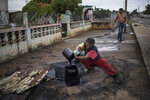 Jose Lugano collects crude oil leaking near the pipes that carry gas to his kitchen, near Lake Maracaibo in Cabimas, Venezuela, May 24, 2019. Nobody lives as closely with the environmental fallout of Venezuela's oil industry as those who scratch out an existence on its perpetually oil-soaked shores. (AP Photo/Rodrigo Abd)