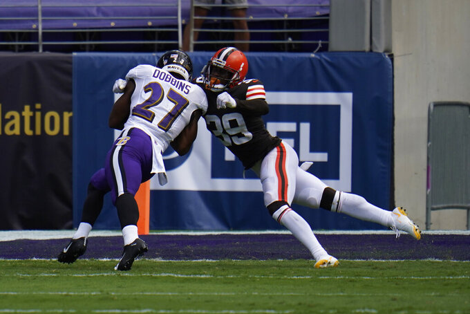 Baltimore Ravens running back J.K. Dobbins (27) scores a touchdown as Cleveland Browns cornerback Terrance Mitchell (39) attempts to tackle, during the first half of an NFL football game, Sunday, Sept. 13, 2020, in Baltimore, MD. (AP Photo/Julio Cortez)