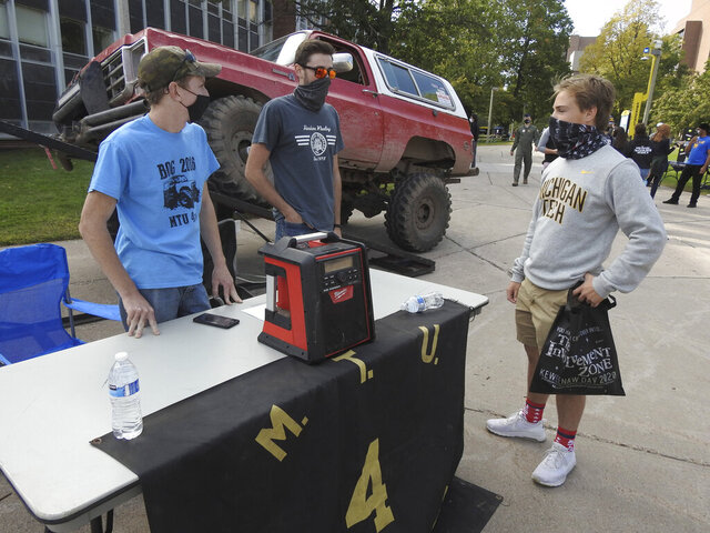 Fred Poddig, from left, and Andrew Gryspeerd, members of Four Wheelers of Michigan Tech, talk to first-year forestry student Braden Berridge during the first K-Day event of the year at Michigan Technological University in Houghton, Mich., Friday, Sept. 11, 2020. Due to COVID-19 restrictions, the university's annual K-Day event, where students get a Friday afternoon off to travel to a local beach and learn about campus activities, was held on-campus and divided into several days. (Garrett Neese/The Mining Journal via AP)