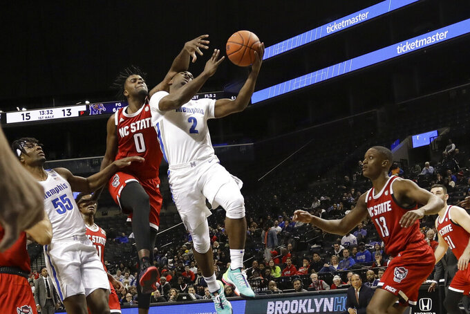 Memphis' Alex Lomax (2) drives past North Carolina State's DJ Funderburk (0) and C.J. Bryce (13) during the first half of an NCAA college basketball game in the Barclays Classic, Thursday, Nov. 28, 2019, in New York. (AP Photo/Frank Franklin II)