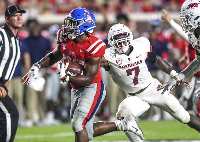 Mississippi running back Scottie Phillips (22) pulls away from Arkansas defensive back Joe Foucha (7) during an NCAA college football game Saturday, Sept. 7, 2019, in Oxford, Miss. (Bruce Newman/The Oxford Eagle via AP)