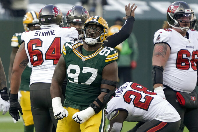 Green Bay Packers' Kenny Clark (97) reacts after sacking Tampa Bay Buccaneers quarterback Tom Brady during the first half of the NFC championship NFL football game in Green Bay, Wis., Sunday, Jan. 24, 2021. (AP Photo/Morry Gash)