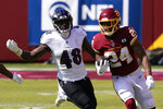 Washington Football Team running back Antonio Gibson (24) runs against Baltimore Ravens inside linebacker Patrick Queen (48) during the first half of an NFL football game, Sunday, Oct. 4, 2020, in Landover, Md. (AP Photo/Susan Walsh)