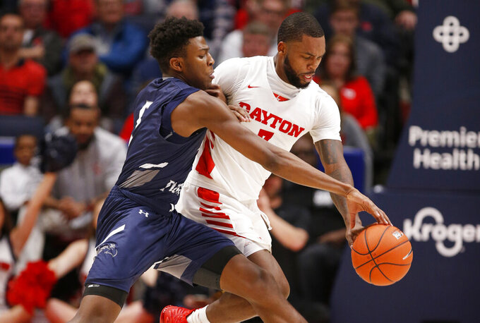 North Florida forward Dorian James, left, and Dayton guard Trey Landers, right, fight for control of the ball during the first half of an NCAA college basketball game, Monday Dec. 30, 2019, in Dayton. (AP Photo/Gary Landers)