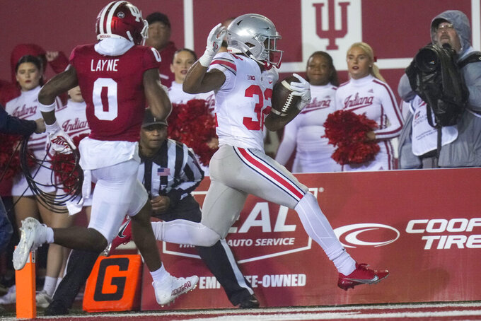 Ohio State running back TreVeyon Henderson (32) scores a touchdown in front of Indiana defensive back Raheem Layne II (0) in the first quarter of an NCAA college football game in Bloomington, Ind., Saturday, Oct. 23, 2021. (AP Photo/AJ Mast)