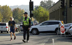 A Lafayette police officer stops traffic for a schoolboy at an intersection that has lost power Monday, Oct. 28, 2019, in Lafayette, Calif. PG&E said Monday its power lines may have started two wildfires over the weekend in the San Francisco Bay Area despite widespread blackouts meant to prevent fires from igniting during dangerously windy weather. (AP Photo/Ben Margot)