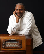 Tavis Smiley, owner of progressive talk radio station KBLA Los Angeles (1580), poses for a portrait on a vintage AM radio in his station's offices, Tuesday, June 15, 2021, in Los Angeles. KBLA's morning drive host Dominique DiPrima gifted Smiley with the radio in celebration of the radio station's launch.(AP Photo/Chris Pizzello)