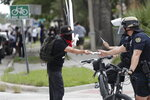 A demonstrator hands out paper dolls to policemen during a protest march over the death of George Floyd, Tuesday, June 2, 2020, in Orlando, Fla. Floyd died after being restrained by Minneapolis police on May 25. (AP Photo/John Raoux)