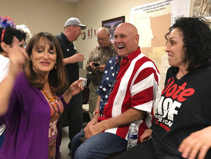 ADDS IDENITY OF WOMAN AT RIGHT AS HEIDI FLEISS -  In this Tuesday, June 12, 2018 photo Nevada brothel owner Dennis Hof, second from right celebrates after winning the primary election in Pahrump, Nev. Hof, the owner of half a dozen legal brothels in Nevada and star of the HBO adult reality series