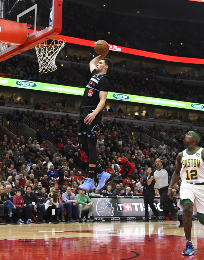 Chicago Bulls guard Zach LaVine (8) goes up for a dunk as Boston Celtics guard Terry Rozier (12) stands nearby during the first half of an NBA basketball game Saturday, Feb. 23, 2019, in Chicago. (AP Photo/David Banks)