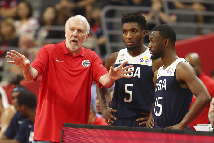 United States' coach Gregg Popovich, left talks to United States' Donovan Mitchell, center and United States' Kemba Walker at right for the FIBA Basketball World Cup in Dongguan in southern China's Guangdong province on Thursday, Sept. 12, 2019. The U.S. will leave the World Cup with its worst finish ever in a major international tournament, assured of finishing no better than seventh after falling to Serbia 94-89 in a consolation playoff game on Thursday night. (AP Photo/Ng Han Guan)