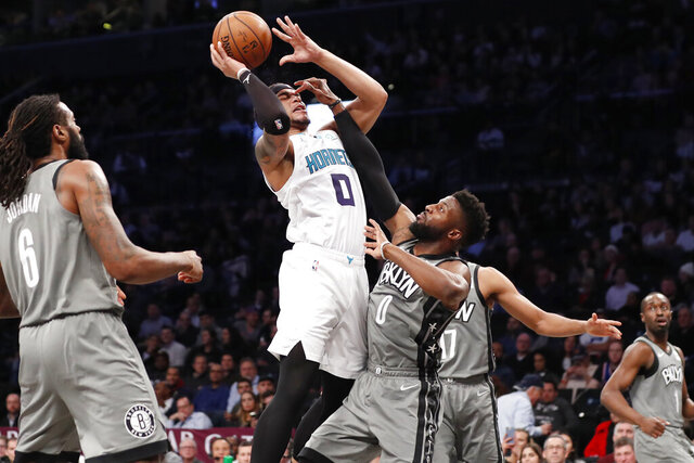 Brooklyn Nets guard David Nwaba (0) defends Charlotte Hornets forward Miles Bridges (0) who goes up for a shot during the first half of an NBA basketball game, Wednesday, Dec. 11, 2019, in New York. (AP Photo/Kathy Willens)