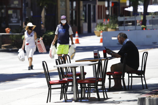 A patron sits at a table set on a street outside of a restaurant Saturday, July 18, 2020, in Burbank, Calif. The city of Burbank has closed off some streets in the downtown district to allow restaurants to expand their outdoor seating arrangements amid the coronavirus pandemic. (AP Photo/Marcio Jose Sanchez)