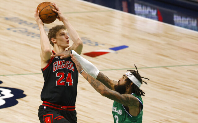 Chicago Bulls forward Lauri Markkanen (24) shoots over Dallas Mavericks center Willie Cauley-Stein (33) during the first half of an NBA basketball game, Sunday, Jan. 17, 2021, in Dallas. (AP Photo/Ron Jenkins)