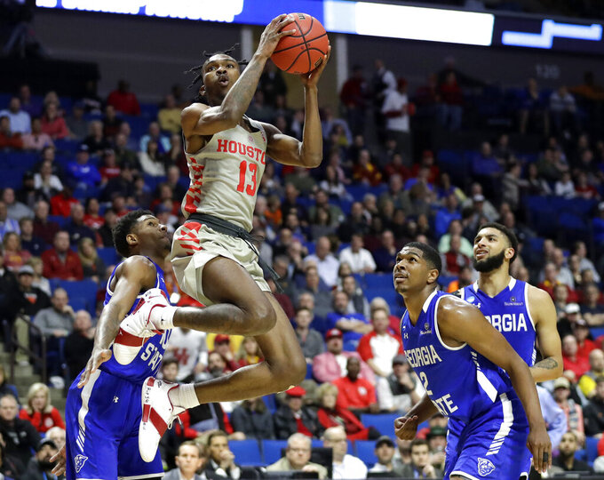 Houston's DeJon Jarreau (13) heads to the basket as Georgia State's Nelson Phillips, left, Malik Benlevi and D'Marcus Simonds, right, watch during the second half of a first round men's college basketball game in the NCAA Tournament Friday, March 22, 2019, in Tulsa, Okla. (AP Photo/Jeff Roberson)