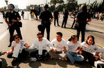 FILE - In this Oct. 23, 1996, file photo, UCLA students, surrounded by Los Angeles police officers, sit on Wilshire Boulevard during an anti-Proposition 209 protest in front of the Federal Building in the Westwood section of Los Angeles. In November 2020, a California with vastly different political preferences and demographics will consider repealing a 1996 law barring state and local governments from discriminating against or granting preferential treatment to people based on race, ethnicity, national origin or sex. If approved, Proposition 16 would repeal a 1996 initiative that made it unlawful for state and local governments to discriminate against or grant preferential treatment to people based on race, ethnicity, national origin or sex. (AP Photo/Frank Wiese, File)