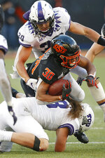 Oklahoma State running back Chuba Hubbard (30) is tackled by TCU linebacker Garret Wallow (30) and linebacker Ben Wilson (18) in the second half of an NCAA college football game in Stillwater, Okla., Saturday, Nov. 2, 2019. (AP Photo/Sue Ogrocki)