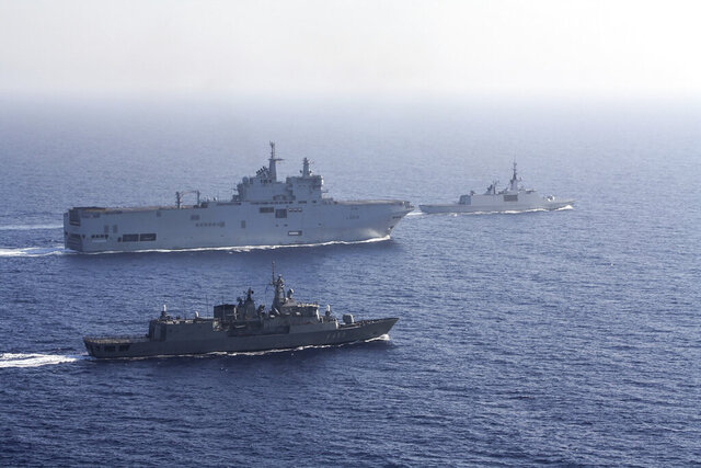 In this photo provided by the Greek National Defence, a French Tonnerre helicopter carrier, rear left is escorted by Greek and French military vessels during a maritime exercise in the Eastern Mediterranean, Thursday, Aug. 13, 2020. Greece's prime minister warmly thanked France for its decision to boost its military presence in the eastern Mediterranean, where Greek and Turkish warships are closely shadowing each other over a Turkish energy exploration bid in waters Athens claims as its own. (Greek National Defence via AP)