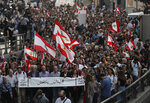 Anti-government protesters march during a protest against the central bank and the Lebanese government, in Beirut, Lebanon, Thursday, Oct. 31, 2019. Lebanese security forces were still struggling to open some roads Thursday as protesters continued their civil disobedience campaign in support of nationwide anti-government demonstrations. The Arabic banner, front, reads: