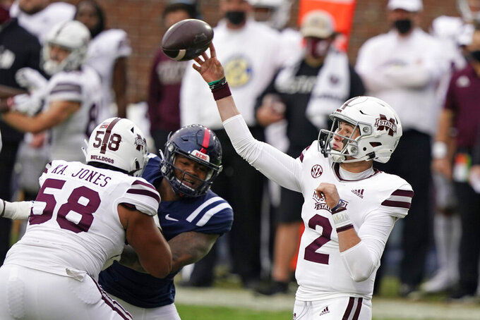 Mississippi State quarterback Will Rogers (2) passes while Kameron Jones (58) blocks a Mississippi player during the first half of an NCAA college football game, Saturday, Nov. 28, 2020, in Oxford, Miss. (AP Photo/Rogelio V. Solis)