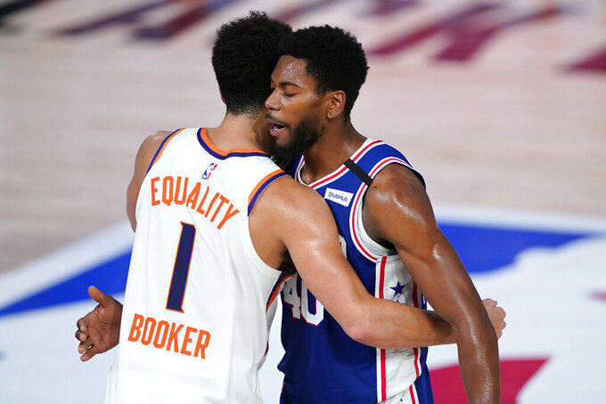 Phoenix Suns guard Devin Booker, left, greets Philadelphia 76ers forward Glenn Robinson III, right, after an NBA basketball game Tuesday, Aug. 11, 2020, in Lake Buena Vista, Fla. (AP Photo/Ashley Landis, Pool)
