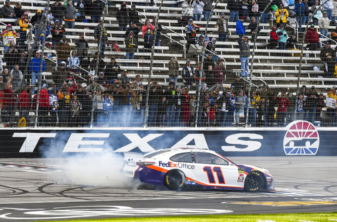 Denny Hamlin celebrates with a burnout after winning a NASCAR Cup auto race at Texas Motor Speedway, Sunday, March 31, 2019, in Fort Worth, Texas. (AP Photo/Randy Holt)