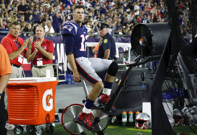 New England Patriots quarterback Tom Brady pedals a stationary bike on the sideline during the second half of the team's NFL preseason football game against the New York Giants, Thursday, Aug. 29, 2019, in Foxborough, Mass. (AP Photo/Elise Amendola)