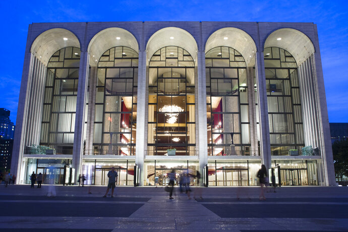 FILE - In this Aug. 1, 2014, file photo, pedestrians make their way in front of the Metropolitan Opera house at New York's Lincoln Center. The Metropolitan Opera will start regular Sunday afternoon performances for the first time in its century-plus history during the 2019-20 season. (AP Poto/John Minchillo, File)