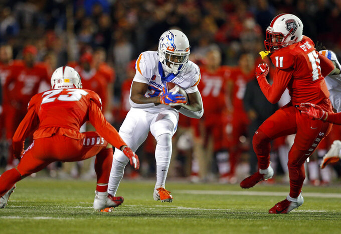 Boise State running back Robert Mahone, center, runs between New Mexico safety Marcus Hayes (23) and linebacker Rhashaun Epting (11) during the first half of an NCAA college football game in Albuquerque, N.M., Friday, Nov. 16, 2018. (AP Photo/Andres Leighton)
