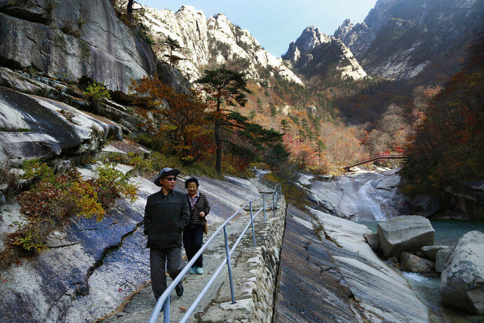 FILE - In this Oct. 23, 2018, file photo, local tourists walk on the trail at Mount Kumgang, known as Diamond Mountain, in North Korea. South Korea said Wednesday, Nov. 6, 2019 it offered to send a delegation to check on facilities at a long-stalled joint tourist resort in North Korea. North Korean leader Kim Jong Un recently ordered the destruction of South Korean-made hotels and other facilities at the North's Diamond Mountain resort, saying they appear