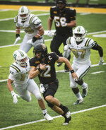 Appalachian State quarterback Zac Thomas (12) breaks away from Charlotte defenders during the third quarter of an NCAA college football game Saturday, Sept. 12, 2020, in Boone, N.C. (Allison Lee Isley/The Winston-Salem Journal via AP)
