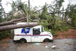CORRECTS YEAR TO 2020 NOT 2019 - Fallen trees rest on a damaged postal truck at an apartment complex where a reported tornado passed through Thursday, Feb. 6, 2020, in Spartanburg, S.C. A powerful winter storm brought severe weather across the Deep South early Thursday, with high winds causing damage that killed one person, injured several others and littered at least four states. (AP Photo/Sean Rayford)