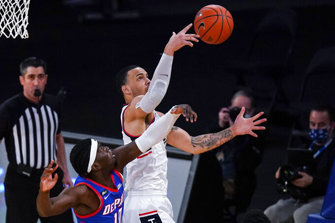 Connecticut's Tyrese Martin, right, fights for control of the ball with DePaul's Ray Salnave during the first half of an NCAA college basketball game in the Big East mens' tournament Thursday, March 11, 2021, in New York. (AP Photo/Frank Franklin II)