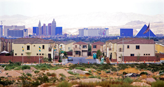 FILE - This Aug. 15, 2005, file photo, shows a housing development with the Las Vegas Strip in the background. Las Vegas-area home prices hit a record high in March, ahead of the economic shutdown prompted by the coronavirus pandemic. Las Vegas Realtors reported Tuesday, April 7, 2020, the median sales price of previously owned single-family homes climbed to $319,000, topping the previous record $316,000 set in February and up 6.3% from March 2019. Home sales were up 5.2% during the month, and up 11.7% for condominiums and townhouses. (AP Photo/Joe Cavaretta, File)
