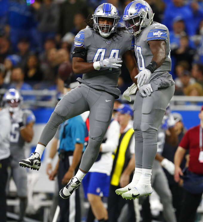 Detroit Lions linebacker Jalen Reeves-Maybin (44) and middle linebacker Jarrad Davis celebrate after a play during the first half of an NFL football game against the Chicago Bears, Thursday, Nov. 28, 2019, in Detroit. (AP Photo/Paul Sancya)