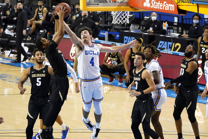 UCLA guard Jaime Jaquez Jr. (4) works for a rebound against Colorado guard Keeshawn Barthelemy, left, during the second half of an NCAA college basketball game Saturday, Jan. 2, 2021, in Los Angeles. (AP Photo/Marcio Jose Sanchez)