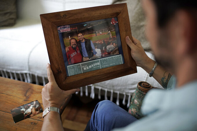 David Biller holds a photo of himself and his father on Friday, Sept. 18, 2020, at his apartment in Rio de Janeiro, Brazil. The photo is from when they watched the Red Sox beat the Yankees in the bottom of the ninth inning on Sept. 11, 2012, at Fenway Park, in Boston. One month later, the author moved to Brazil. (AP Photo/Silvia Izquierdo)