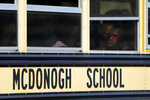 A child is visible through a window as a school bus leaves the McDonogh School campus after a reported explosion, Wednesday, Sept. 18, 2019, in Owings Mills, Md. An explosion in the boiler room injured a child and two adults, according to reports. An email from a school spokeswoman to parents said a boiler room explosion blew off the top part of a building's smokestack. (AP Photo/Julio Cortez)