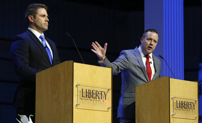 FILE - In this April 19, 2018 file photo Republican primary senatorial candidate Corey Stewart, right, gestures as Del. Nick Freitas listens during a debate at Liberty University in Lynchburg, Va.  The vicious tenor of the 2016 GOP presidential primary is being matched by Virginia's raucous congressional primaries. In primaries for the U.S. House and the Senate seat held by Democratic Tim Kaine, there's been a near constant stream of complaints of below-the-belt attacks or shady campaigning. Some candidates bemoan the negative tone while others say it's not a problem.  (AP Photo/Steve Helber)