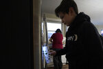 Kari Wegg, background, continues making breakfast as her youngest son, Gunnar, gets water from the refrigerator before catching a bus for school in their Westfield, Ind., home on Tuesday, March 23, 2021. (AP Photo/Charles Rex Arbogast)