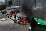 A protester burns tires and garbage containers, as he blocks a main highway, during a protest against the increase in prices of consumer goods and the crash of the local currency, in Beirut, Lebanon, Thursday, June 17, 2021. Shops, government offices, businesses and banks shut their doors Thursday in response to a call for a general strike by Lebanon's main labor union. (AP Photo/Hussein Malla)