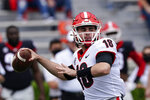 """FILE - Georgia quarterback JT Daniels (18) throw a pass in the first half during Georgia's spring NCAA college football game in Athlens, Ga., in this Saturday, April 17, 2021, file photo. Monken believes his Georgia offense is """"just so further ahead"""" than a year ago as it enters its first full season with JT Daniels at quarterback. The offense thrived in the Bulldogs' 4-0 finish after Daniels took over as the starter last season. Now, the continuity provided by Monken's second season as offensive coordinator and Daniels' return has fueled No. 5 Georgia's championship hopes for 2021. (AP Photo/John Bazemore, File)"""