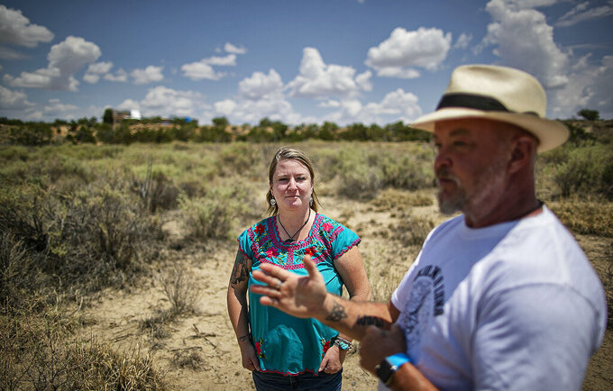 Cid Isbell, right, and Medina Isbell talk about their plans to truck in water for the small cannabis farm they are building on 30 acres Wednesday, July 14, 2021 outside of Cerrillos, N.M. They are among many hopeful entrepreneurs who see New Mexico's upcoming legal market for cannabis production and sales — set to launch by April 1 — as a way to break into a new business with a potential windfall. (Jim Weber/Santa Fe New Mexican via AP)