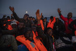 Migrants and refugees from different African nationalities sailing adrift on an overcrowded rubber boat, receive life jackets from aid workers of the Spanish NGO Open Arms in the Mediterranean Sea, international waters, off the Libyan coast, Friday, Jan. 10, 2020. (AP Photo/Santi Palacios)