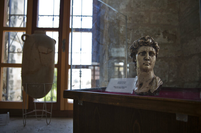 In this July 16, 2019 photo, an ancient bust of King David is displayed inside the historical Pasha Palace run by Gaza's Ministry of Tourism and Antiquities, in Gaza City. Gaza was a major trade route between Egypt and the Levant for thousands of years, but decades of uprisings, war and political turmoil have inflicted a heavy toll on its rich archaeological heritage, exposing it to looting and destruction. Neglect by Hamas authorities and a blockade imposed by Israel and Egypt have hindered efforts to preserve and protect antiquities, leaving much of the work to private collectors. (AP Photo/Khalil Hamra)