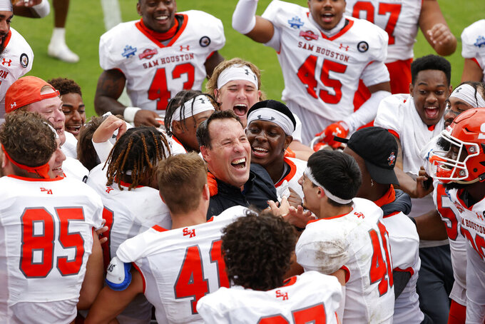 FILE - Sam Houston State head coach K.C. Keeler, center, is swarmed by his team after they defeated South Dakota State in the NCAA college FCS Football Championship in Frisco, Texas, in this Sunday May 16, 2021, file photo. Sam Houston State won 23-21. Keeler didn't ask his Sam Houston players to stick around long after they won the school's first FCS national championship last May, capping a long and draining season — physically and emotionally — because of the pandemic. He's also not asking them to stick around as long at practice this year. Throughout the Championship Subdivision, coaches are making concessions this fall to acknowledge that the quick turnaround from last spring is hard. (AP Photo/Michael Ainsworth, File)
