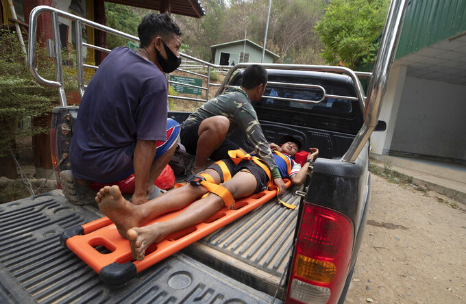 An injured Karen villager from Myanmar is transported at Ban Mae Sam Laep Health Center, Mae Hong Son province, northern Thailand, after crossing Salawin river on a boat, on Tuesday March 30, 2021. The weekend strikes by the Myanmar military, which sent ethnic Karen people seeking safety in Thailand, represented another escalation in the violent crackdown by Myanmar's junta on protests of its Feb. 1 takeover.(AP Photo/Sakchai Lalit)