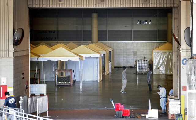 Workers prepare the Ernest N. Morial Convention Center Hall J on Friday, March 27, 2020, in New Orleans after Louisiana state health officials said they are planning to put more than 1,100 beds in the makeshift hospital for patients with the coronavirus. (David Grunfeld/The Advocate via AP)