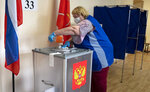 A polling station employee wearing a face mask and gloves to protect against coronavirus disinfects a ballot box at a polling station in St.Petersburg, Russia, Thursday, June 25, 2020. Polls have opened in Russia on Thursday for a week-long vote on a constitutional reform that may allow President Vladimir Putin to stay in power until 2036. (AP Photo/Dmitri Lovetsky)