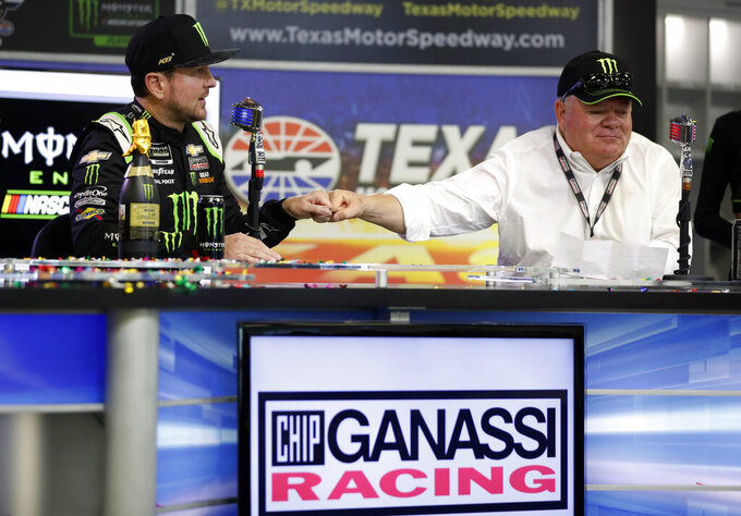 Kurt Busch, left, and team owner Chip Ganassi, right, celebrate after announcing a multi-year contract for Busch during a NASCAR news conference at Texas Motor Speedway in Fort Worth, Texas, Saturday, Nov. 2, 2019. (AP Photo/Roger Steinman)